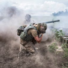 UKRAINE, Shyrokyne: Linsa, his warname, shooting with the anti-tank grenade launcher. Next to him, his comrade Andrei is blocking his ears as the noise of the shooting is very high. Linsa is targeting some tanks that they have seen on the separatist side of Shyrokyne. June 26, 2015.